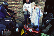 Group of teenage boys huddled around a scooter Lambeth Walk South London c.2000