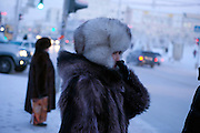 Woman with fur clothes protected against the cold close to Lenin Square in the city of Yakutsk. Yakutsk is a city in the Russian Far East, located about 4 degrees (450 kilometres) south of the Arctic Circle. It is the capital of the Sakha (Yakutia) Republic in Russia with a major port on the Lena River. The city has a population of 264.000 (2009). Yakutsk is one of the coldest cities on Earth. The average monthly winter temperature in January is around -43,2 C. Yakutsk, Jakutsk, Yakutia, Russian Federation, Russia, RUS, 15.01.2010.