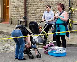 © Licensed to London News Pictures. 27/06/2012. Oldham , UK . A large explosion , believed to be caused by gas , has brought down at least one house in an Oldham terrace. Evacuated residents are not allowed back in to their homes and many wait at the edge of the police cordon . Photo credit : Joel Goodman/LNP