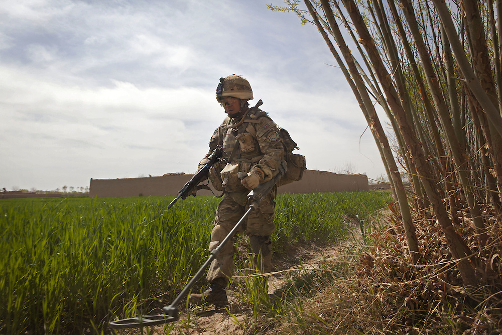 A British soldier of 4PARA sweeps the ground for IED's and mines as other soldiers from 3PARA take up defensive positions and form a secure cordon whilst on patrol in Nad Ali, Hemand Province, Afghanistan on the 11th of March 2011.