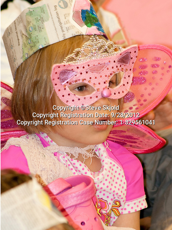 Young female student in fairy costume and mask in a classroom recycling program. Horace Mann School St Paul Minnesota MN USA