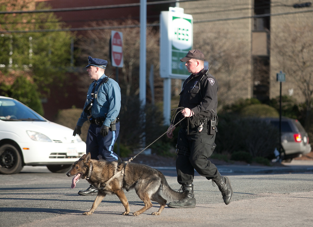 Needham, MA 03/27/2012.State Police officers and a K-9 search the area of the Hess gas station on Highland Ave. after an armed robbery at Pittsburgh Paints on Tuesday afternoon..Wicked Local Photo by Alex Jones