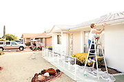 """Laverne """"Cookie"""" Hunting paints the trim of her home in Sun City, Arizona December 8, 2010. Cookie bought the home, which was built in Sun City's first year in 1960, from her parents who have since passed away."""