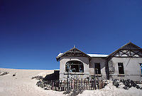 A deserted house surrounded by desert in the ghost town of Kolmanskop, an abandoned diamond mine.