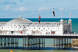 © Licensed to London News Pictures. 09/09/2017. Brighton, UK. Members of the public take a ride on Brighton's newest zip-wire attraction on the beach. Photo credit: Hugo Michiels/LNP