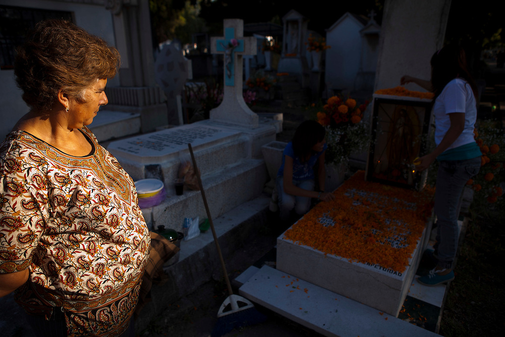 "A women watches her daughters decorate a family members grave with Cempasuchil (Marigold) Flowers which are traditionally used at a cemetery in the town of Zacapu, Michoacan, Mexico, on Nov. 2, 2011, as part of the celebration of the deceased life on ""Noche de Muertos"" (Day of the Dead), a cheerful and solemn occasion. ..©Benjamin B Morris"