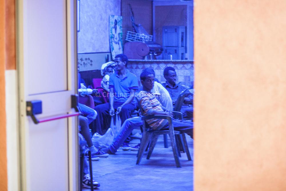 Quasi 800 profughi di cui più di 100 bambini vengono ospitati nella struttura di accoglienza Baobab di Via Cupa a Roma. La struttura può accogliere circa 220 migranti. Semplici cittadini e il gruppo SEL hanno raccolto generi alimentari da distribuire agli all'interno della struttura. Nel centro Baobab ragazzi guardano la TV in una stanza con luci azzurre.
