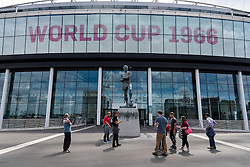 © Licensed to London News Pictures. 30/07/2016. Football fans pose for photos next to the bronze statue of England footballer BOBBY MOORE outside Wembley Stadium on the 50th anniversary of England beating Germany in the World Cup finals on 30th July 1966.  London, UK. Photo credit: Ray Tang/LNP