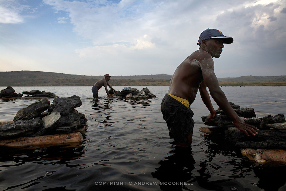 Men return to shore with their day's haul of rock salt, at Lake Katwe, Uganda. Rock salt is harvested from the main body of the lake three days a week with workers paid by weight at approximately $2 per 100kg, of which the government takes a percenage. All men work from dusk till dawn with a strong worker extracting 400 kg per day. Skin damage is a major problem for people working at Lake Katwe as chemicals in the water eat away at any nick or cut and also cause nerve damage.