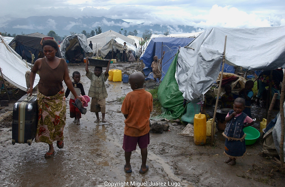 Kiwanja, Congo--Thousans of displaced people are trapped behind rebel lines in Eastern Congo, awaiting help from aid groups. Rebel leader Laurent Nkunda has urged people to return home, as this woman and her children are doing. (Photo by Miguel Juárez Lugo).