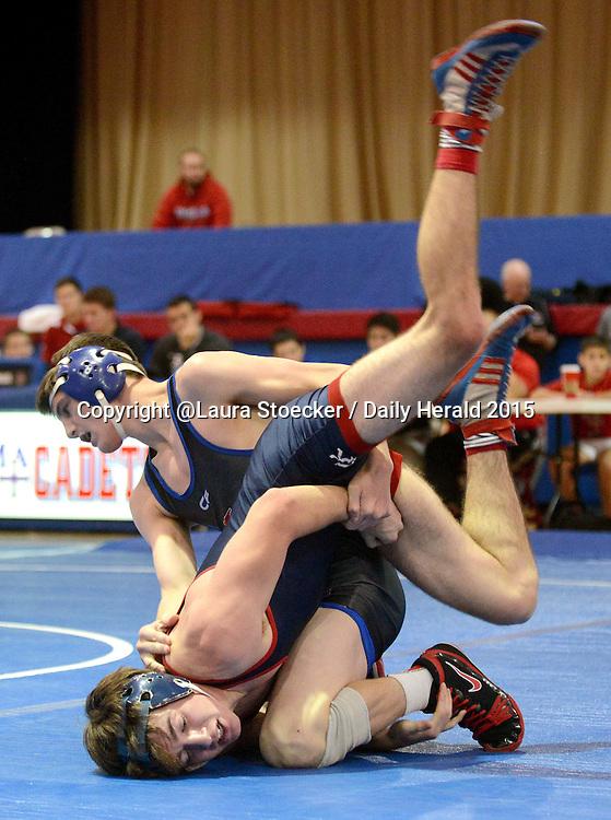 Laura Stoecker/lstoecker@dailyherald.com<br /> Marmion Academy's Peter Ferraro takes St. Rita's Mike Scully in the 138 pound match in Aurora Saturday.