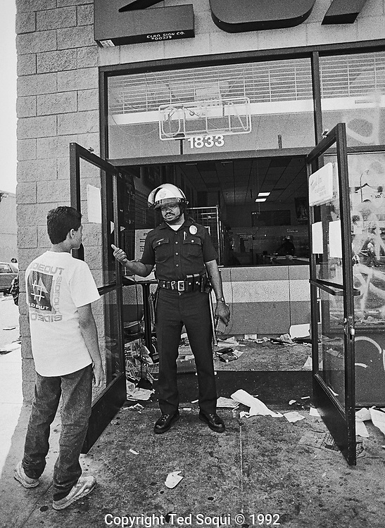 A lone LADP officer tells someone to beat it in front os a 20/20 video rental store.