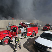 Firemen begin to assemble at the south end of American Furniture on Friday as they try and stop a fire from spreading to the few remaining building at their facility in Ecru.