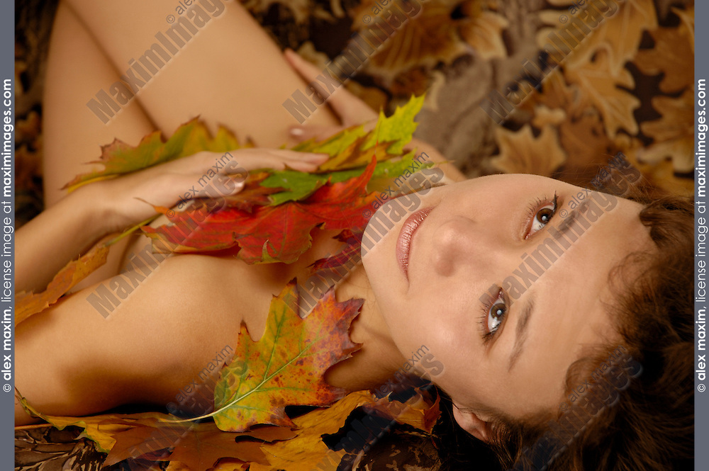 Naked woman with beautiful expressive eyes and sad wistful look lying in colorful autumn leaves.