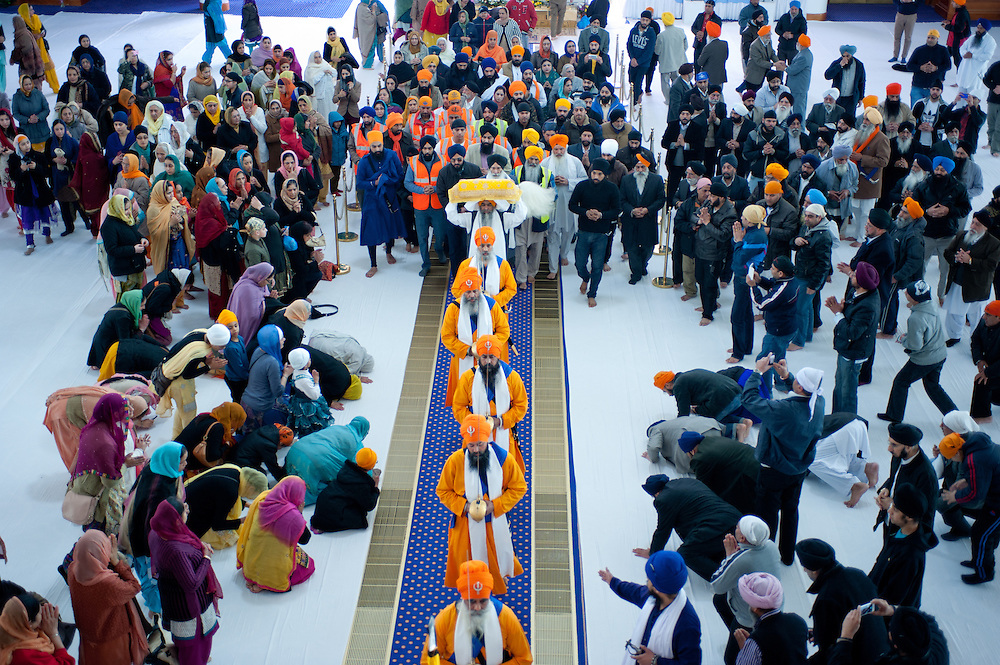 London, UK - 7 April 2013: Panj Piare exit the gundwara followed by the Guru Granth Sahib, the holy Sikh scripture, which is placed on a float.