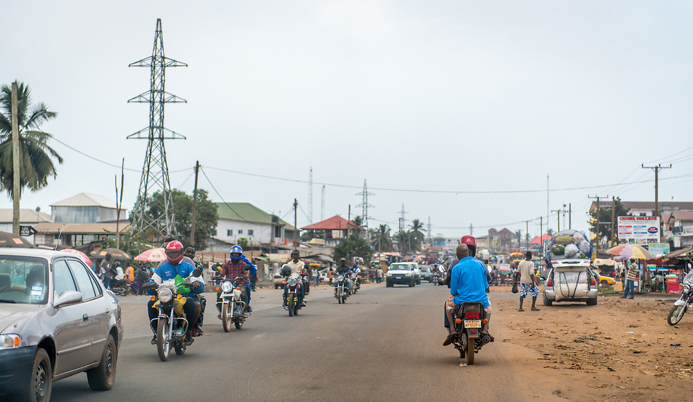 A line of motorists travel down a bustling street in the city of Monrovia, Liberia