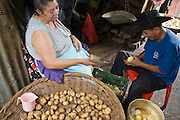 08 JANUARY 2007 - MANAGUA, NICARAGUA:  A couple peel potatoes in their stall in the Mercado Oriental, the main market that serves Managua, Nicaragua. The market encompasses dozens of square blocks and is the largest market in Central America. Many people in Nicaragua shop every day because they don't have refrigeration in their homes and the market is a beehive of activity.        PHOTO BY JACK KURTZ