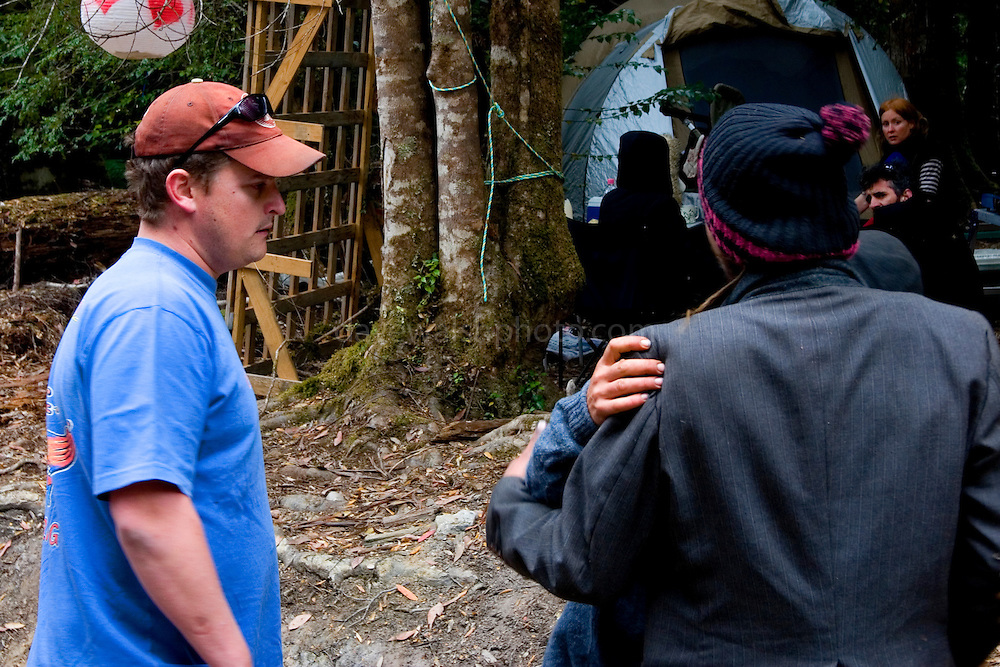 A logging contractor, left, gets angry about a crippled dog belonging to one of the protestors. The logger, who is visiting the camp, wants the dog to be put down, or shot to put it out of its misery. An activist right, is restrained by a friend.