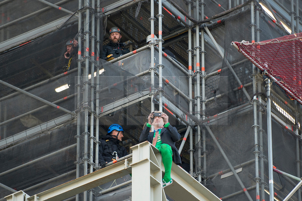 © Licensed to London News Pictures. 18/10/2019. LONDON, UK.  A climate activist (green tights) from Extinction Rebellion takes a photo on his mobile phone after scaling the construction scaffolding of the Queen Elizabeth Tower in Westminster.  Parliament Square and the surrounding area has been brought to a standstill as police and emergency services assess the situation.  Photo credit: Stephen Chung/LNP