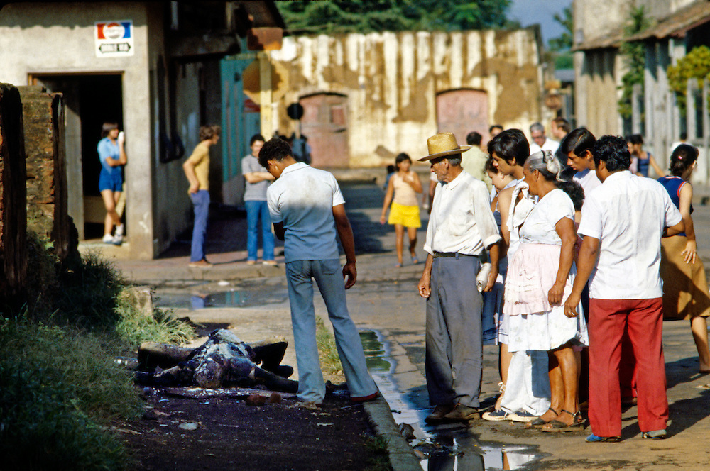 Masaya, Nicaragua townspeople stare at the burned and charred body of a Nicaragua National Guardsman after house to house street fighting in Civil War in Nicaragua - 1978.