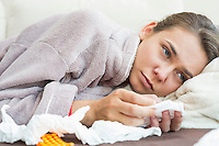 Sick woman with tissue and medicines lying on bed