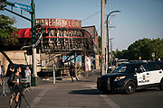 Minneapolis Police officers drive past the charred remains of the Minnehaha Liquor store along Lake Street in Minneapolis, Minnesota on Monday, June 1, 2020.