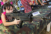 "11 JANUARY 2014 - BANGKOK, THAILAND:  A Thai girl plays with a TAVOR Assault Rifle during Children's Day in Bangkok. The Royal Thai Army hosted a ""Children's Day"" event at the 2nd Cavalry King's Guard Division base in Bangkok. Children had an opportunity to look at military weapons, climb around on tanks, artillery pieces and helicopters and look at battlefield medical facilities. The Children's Day fair comes amidst political strife and concerns of a possible coup in Thailand. Earlier in the week, the Thai army announced that movements of armored vehicles through Bangkok were not in preparation of a coup, but were moving equipment into position for Children's Day.     PHOTO BY JACK KURTZ"