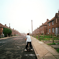 Susie's son Ben on his street on the Ford Estate in Sunderland where many families live below the poverty line. Susie doesn't like her children playing outside because the area is full of people smoking drugs and hanging around. Most of the houses in the estate are boarded up and attract drug dealers.