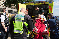 © Licensed to London News Pictures. 20/08/2013.  A man who was rescued from the water in the River Thames near St Katharines Pier is attended by emergency services and taken conscious in an ambulance for further treatment. Photo credit : Vickie Flores/LNP