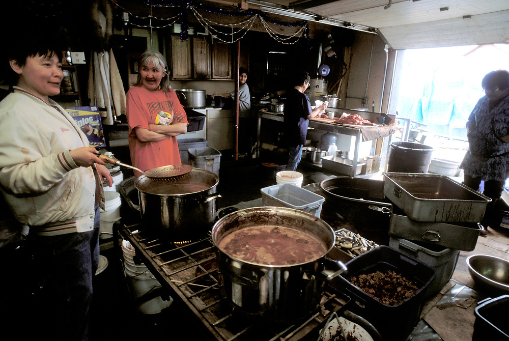 Barrow, Alaska, Women working together to prepare a feast of whale meat and blubber for a traditioal feast celebrating a successful bowhead whale hunt. the feast is held at the whaling captain's house and all members of the community are welcome.