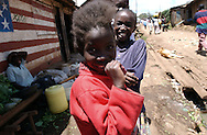 Two young girls pause for the photographer along a main road in the Kibera slum of Nairobi, Kenya in November 2002. Population estimates in Kibera range from 200,000 - 800,000 people who live among the rooftops of corrugated tin and adobe-mud walled structures in the East African country's capital city.