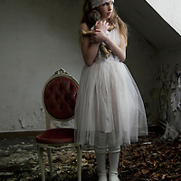 little girl holding doll in a abandoned room of decay
