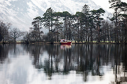 © Licensed to London News Pictures. 19/01/2016. Ullswater UK. Picture shows the snow covered hills reflecting in the mirror like surface of Ullswater lake this morning. Photo credit: Andrew McCaren/LNP