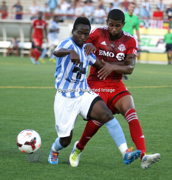 Wilmington Hammerheads FC's Sunny Jane challenges Toronto FC's Jeremy Hall Wednesday June 18, 2014 at Legion Stadium in Wilmington, N.C. (Jason A. Frizzelle)