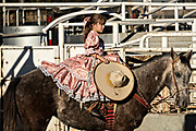 Analia Franco with the legendary Franco family of Charro champions, rides a horse sidesaddle wearing the traditional Adelita costume during a Mexican rodeo practice session in the Jalisco Highlands town of Capilla de Guadalupe, Mexico. Women participants in the traditional Charreada are called Escaramuza and perform precision equestrian displays riding sidesaddle and garbed in Adelita dress.