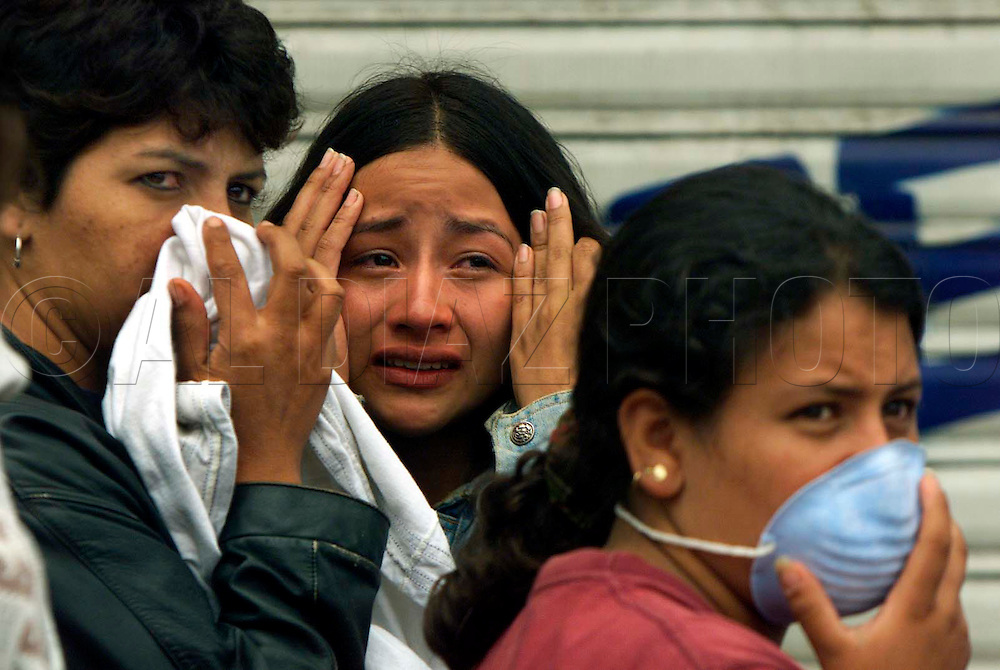 1/28/99 Al Diaz/Herald staff--l to r are, Aydee Gutierrez, Ludivia Vargas, Paola Andrea.<br /> Vargas reacts after her husband was found buried inside their apartment in Armenia. The women on either side are friends watching the search for more victims.