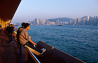 People view the city skyline and Victoria Harbour from the Promenade in Kowloon, Hong Kong, China.
