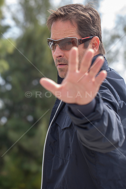 man walking down the street with his hand held out in front of his face