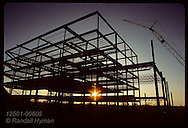 Evening sun peeks between girders of office bldg being built in St. Louis' West County area. Missouri