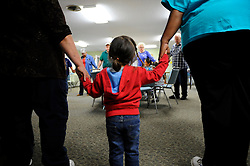 A prayer circle at the Vineyard Church in east Salinas, which runs a bi-monthly food distribution program in collaboration with the Food Bank of Monterey County.