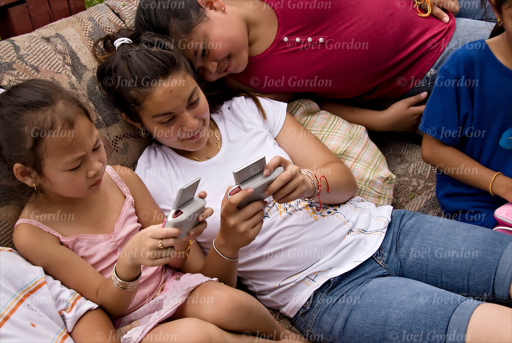 """Young Asian American children using cellphone to text message their friends.Text messaging, or texting is the common term for the sending of """"short"""" (160 characters or fewer, including spaces) text messages from mobile phones using the Short Message Service (SMS). It is available on most digital mobile phones and some personal digital assistants with on-board wireless telecommunications. The individual messages which are sent are called text messages, or in the more colloquial text speak texts."""
