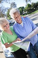 Two senior women reading map, smiling