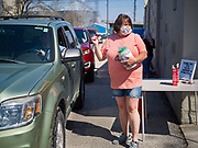 "26 APRIL 2020 - JEWELL, IOWA: MISCHELLE HARDY, talks to people who bought ""grab and go"" roast pork dinners in Jewell during a fund raiser Sunday. Jewell, a small community in central Iowa, became a food desert when the only grocery store in town closed in 2019. It served four communities within a 20 mile radius of Jewell. Some of the town's residents are trying to reopen the store, they are selling shares to form a co-op, and they hold regular fund raisers. Sunday, they served 550 ""grab and go"" pork roast dinners. They charged a free will donation for the dinners. Despite the state wide restriction on large gatherings because of the COVID-19 pandemic, the event drew hundreds of people, who stayed in their cars while volunteers wearing masks collected money and brought food out to them. Organizers say they've raised about $180,000 of their $225,000 goal and they hope to open the new grocery store before summer.           PHOTO BY JACK KURTZ"