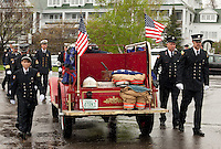 Members of the Meredith Fire Department surround the antique Model A as they arrive at Hesky Park for the memorial service for retired Chief Charles G. Palm Sunday afternoon.   (Karen Bobotas/for the Laconia Daily Sun)