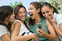 Four women laughing at mobile phone display.