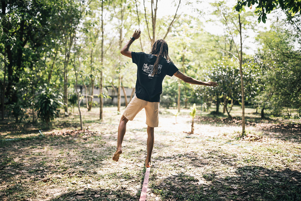 Chiang Mai, Thailand -- May 20, 2017: Will Hardy, 31, the owner of Suan Sati, balancing on a slack line at his yoga retreat in northern Thailand.