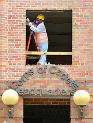 A worker dressed in protective gear scrapes away at a window seal on the second floor of the Quads Dorm 2 building as construction on a massive renovation project continues on the Texas A&M campus.  Dorm buildings 1-5 have been closed until August of 2016 when the renovations are expected to be complete and members of the Corps of Cadets have been relocated to The Commons and other Corps dorm buildings until this time.