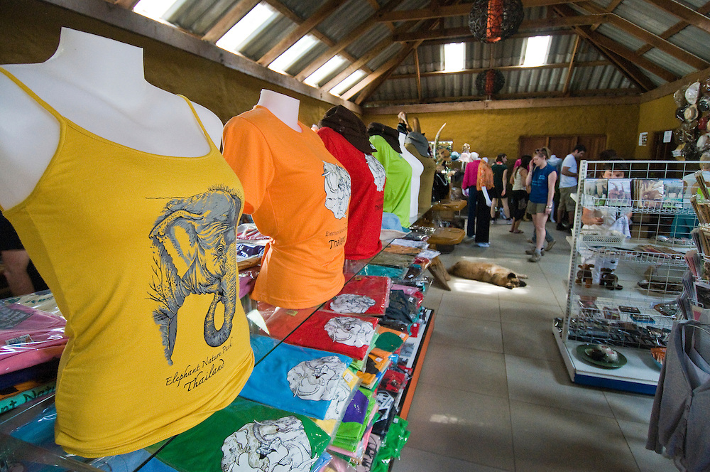 "Tourists in the gift shop at the Elephant Nature Park near Chiang Mai, Thailand.  Sangduen ""Lek"" Chailert founded the park as a sanctuary and rescue centre for elephants.  The park currently has 32 elephants sponsored and supported by volunteers from all over the world."
