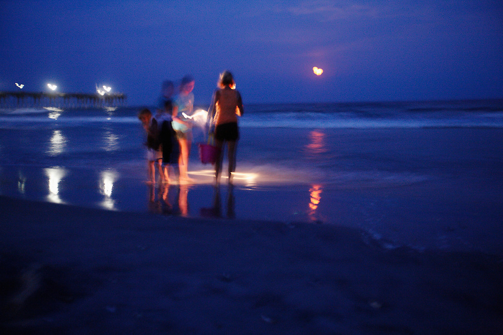 People with flashlights look for seashells after dusk on Wrightsville Beach at night in this long-exposure shot.