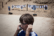 One of the Sarosi family sons protect his hears before a shooting training just after he learned how to handle a gun properly.